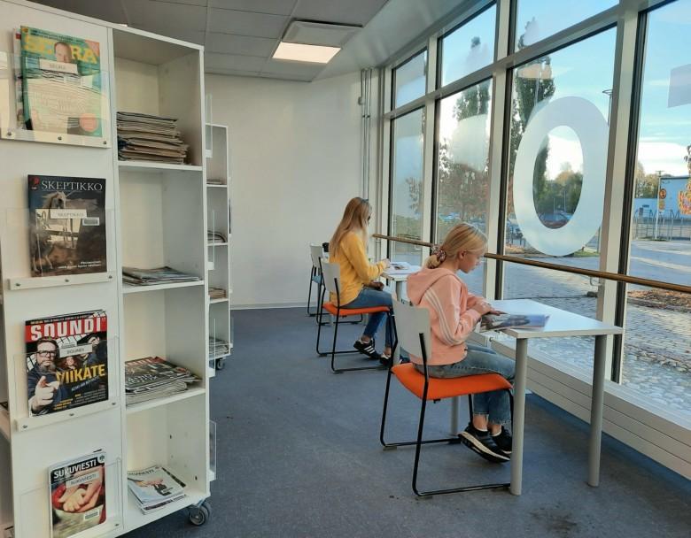 Lehdenlukijoita kirjaston omatoimialueella