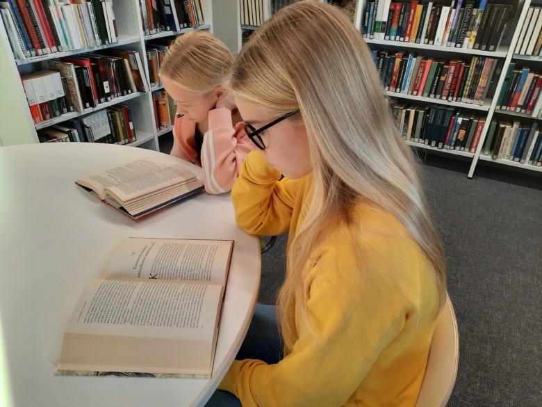 Asiakkaita lukemassa kirjastossa