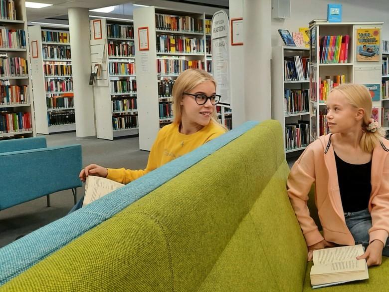 Lukijoita kirjaston nuorten osaston sohvilla