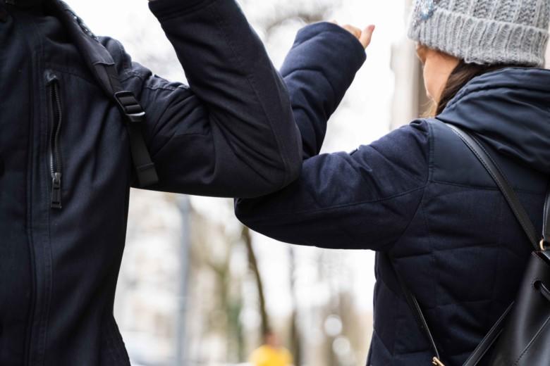 Kaksi henkilötervehtii toisiaan siten, että kyynärpäät koskettavat ja turvaetäisyys säilyy.
