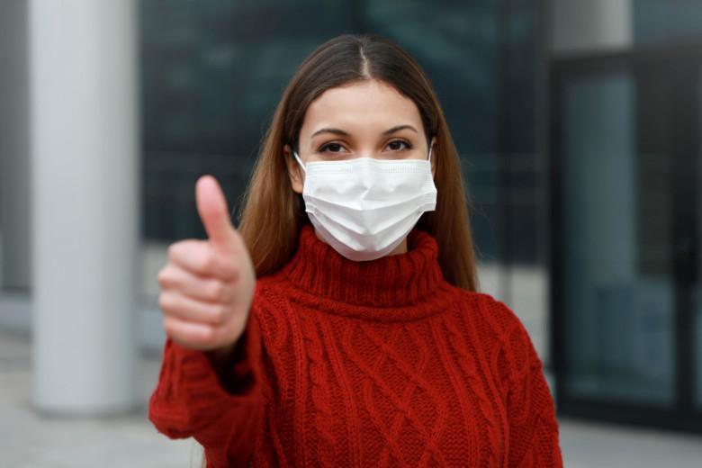 Nuori nainen maski kasvoillaan näyttää peukkua.