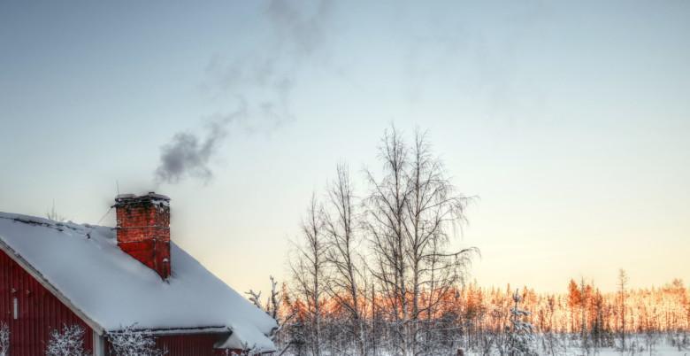 Omakotitalon savupiipusta nousee savua lumisessa talvisäässä.