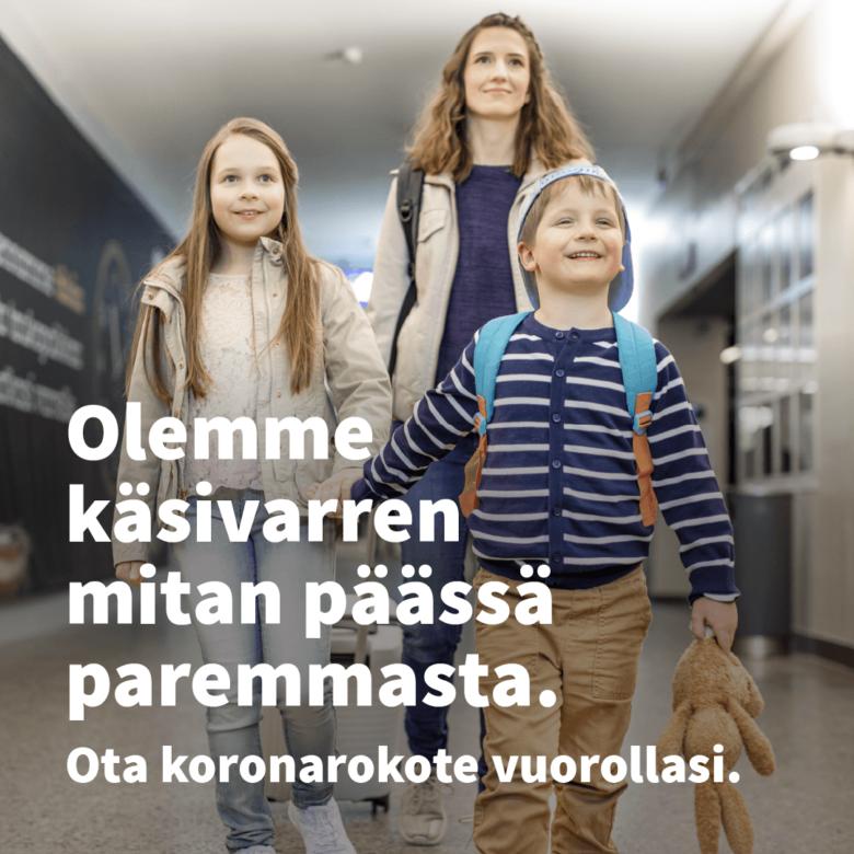 Nainen ja kaksi lasta kävelevät hymyillen pitkin käytävää. Teksti Olemme käsivarren mitan päässä paremmasta. Ota koronarokotus vuorollasi.