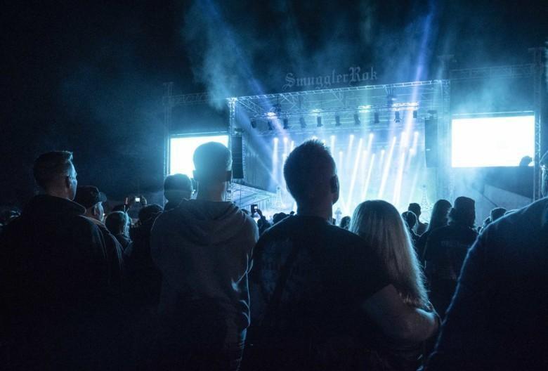 Yleisö kuuntelee Smugglerrokin lavaesiintyjää iltapimeässä,