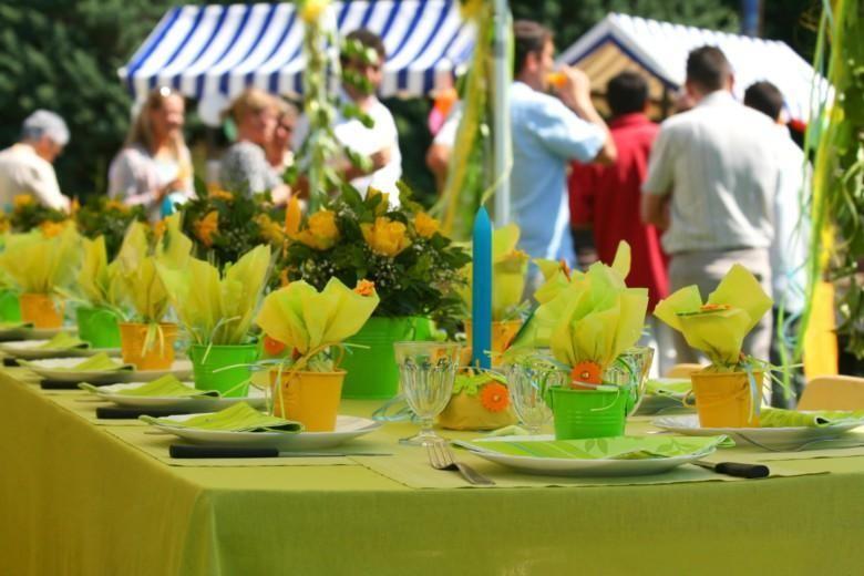 Puutarhajuhlissa katettu pöytä ja ihmisiä taustalla.