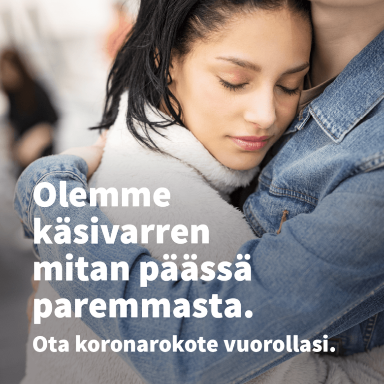 Nuori nainen ja mies halaavat toisiaan. Teksti: Olemme käsivarren mitan päässä paremmasta. Ota koronarokote vuorollasi.