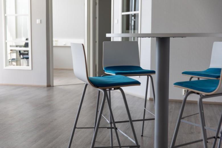 Toimistohotellin sisätiloissa pyöreän pöydän ympärillä tuolit sinisellä kangaspehmusteella.