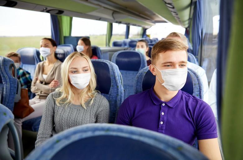 Matkustajia linja-autossa maskit kasvoillaan.