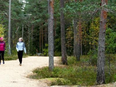 Kaksi naista kävelee syksyisellä ulkoiluradalla.