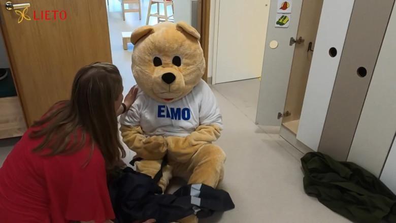 Elmo-nalle istuu lattialla, päiväkodin hoitotäti juttelee hänen kanssaan.
