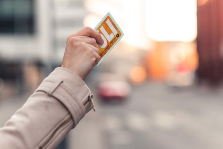 Nuoren naisen käsi heilauttaa Föli-korttia pysäyttääkseen bussin.