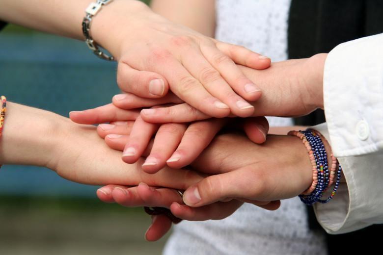 Kolmen ihmisen kädet vuorotellen päällekkäin.
